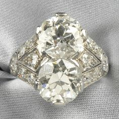 Art Deco Platinum and Diamond Twin-stone Ring, set with two old mine-cut diamonds weighing approx. 2.60 and 2.80 cts., further set with old European-cut diamonds, approx. total wt. 5.80 cts., millegrain accents, size 5 3/4.
