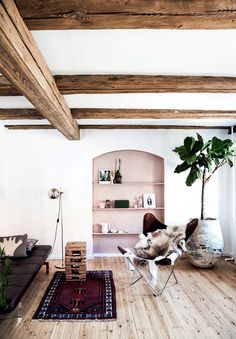 Scandinavian living space with exposed wooden ceiling beams, a rose painted bookshelf, and a butterfly chair