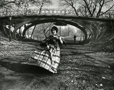 Old-world charm: Sherman is seen in a voluminous checkered dress with a tiny parasol strolling through a windswept Central Park, framed by t...