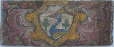 """• TAVOLA VII ter cm 45 x 18,3 x 2,7 BLASONE CON PAVONE Nella parte posteriore della tavola, diverse lesioni e fori di tarlo, e gallerie """"a tarlo lungo"""", e molti fori presumibilmente prodotti da chiodi; la pellicola pittorica è in condizioni discrete, a zone fragile. Blasone a scudo sagomato contenente un pavone raffigurato a mezzobusto e di profilo verso sinistra, in azzurro e giallo oro, affiancato da due ghiande rivolte verso l'alto. Lo sfondo dello scudo è bianco e la cornice che lo…"""