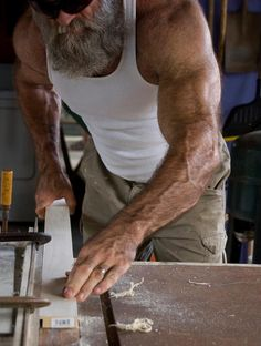 I don't know what this guy is doing with that piece of trim, but he is jacked out of his mind and has a sick beard even though he is old. Respect.