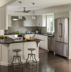 Small, chic kitchen features a Minka Aire ceiling fan cooling extra light gray cabinets paired with black quartz countertops and a linear gray tile backsplash.