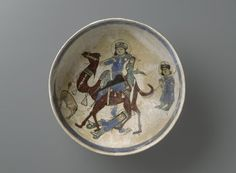 Medium: Ceramic, mina'i (enameled) or haft rangi (seven colors) ware; fritware, in-glaze painted in blue, green, and brown on an opaque white glaze, overglaze painted in black Geographical Locations: Place made: Iran Possible place made: Kashan, Iran Dates: late 12th - early 13th century Dynasty: Seljuq Dynasty Period: Seljuq Period Dimensions: height x diameter: 4 x 8 5/16 in. (10.2 x 21.1 cm) thickness: 1/8 in. (0.3 cm)  (show scale) Collections:Arts of the Islamic World