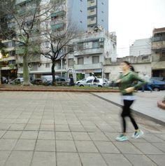 Chica corriendo. Se puede apreciar el movimiento de ella comparado con la quietud del parque en el fondo.