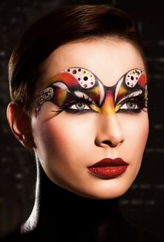 Artistic orange, red, gold and brown fantasy makeup look with gem accents.