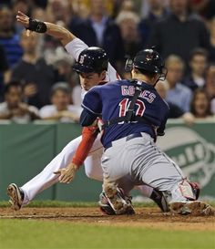 Boston Red Sox Jacoby Ellsbury, left, reaches down towards home plate as he is tagged out by Cleveland Indians catcher Yan Gomes on a single by Dustin Pedroia during the third inning of a baseball game at Fenway Park in Boston, Thursday, May 23, 2013. (AP Photo/Charles Krupa)