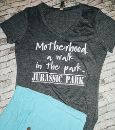 Custom Tees - Super Soft V-Neck Motherhood. A walk in the park. Jurassic Park. T-shirt White text. All shirts are made to order and we hand pick soft materials. This is not your dollar tees. I only use high quality stretch vinyl heat pressed onto your shirts. We use white text