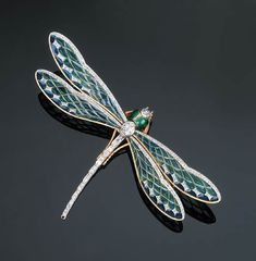 An Attractive Plique-à-Jour Enamel Dragonfly Brooch   The insect with tapering diamond-set body between green and blue plique-à-jour enamel wings with rose-cut diamond upper edge, rose and old-cut diamond detail to green enamel head above textured legs, with French assay and indistinct maker's mark, 12.0 cm wide