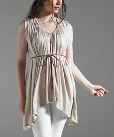 Elegant and posh, this neutral sleeveless top will be a perfect pick for making a chic statement. A lavish fabric, a hi-low silhouette and gathering craft a drapey look.95% rayon / 5% jersey spandexMachine wash; dry flatMade in the USA