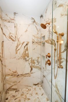Gold and white marble-look shower tile in white bathroom with gold fixtures. Shower Tile, Bathroom Interior Design, Glass Shower Doors, Shower Doors, Custom Door, White Bathroom, Gold Fixtures, White Marble, Glass