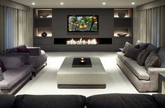Sleek, modern living room. I love that back wall with the fire feature, large tv, and recessed, lit storage spots!