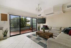 Casual living room with ceramic tile flooring and large sliding doors to patio.