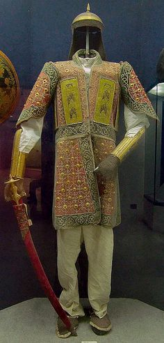 Chilta hazar masha (coat of a thousand nails),  kulah khud (helmet), bazu band (arm guards), talwar (sword), 18th century. Indian armored clothing made from layers of fabric faced with velvet and studded with numerous small brass nails, which were often gilded. This example has additional armor plates in the chest area. Fabric armor was very popular in India because metal became very hot under the Indian sun.  National Museum of India, New Delhi.