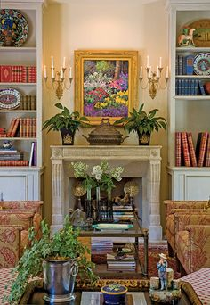 Rich blooms of color make for a lively library. Lush greenery brings to life a vibrant oil painting above an antique limestone Regency fireplace. The antique metal tureen on the mantel gives this room the feel of a garden greenhouse, while the candelabras on either side offer natural lighting, even on a gloomy day.
