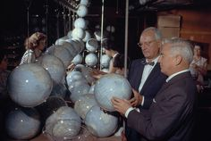 Melville B. Grosvenor, Editor of the Magazine and President of the Society, admires new globes on a conveyor belt in a Chicago plant, December 1961.