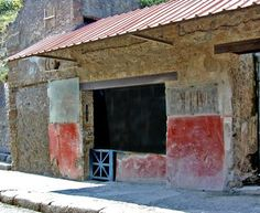 """Pompeii: Thermopolium of Asellina. One of the most complete examples. The wide doorway was open to the street, the bottom floor served as a """"fast-food"""" restaurant, and the second floor had rooms for rent. Inside, jugs, dishes, and a kettle were found intact."""
