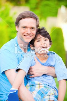 Handsome father holding smiling disabled son outdoors Royalty Free Stock Photo