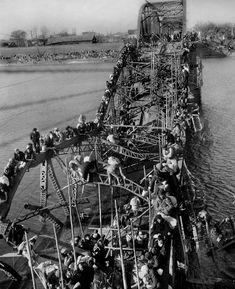 Les habitants de Pyongyang fuient vers le sud alors que les troupes chinoises descendent du nord. Ils sont prêts à escalader de façon périlleuse un pont en ruine traversant la rivière Taedong.  -- Photo prise le 4 décembre 1950