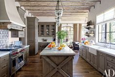 Antique Tunisian tile from Exquisite Surfaces makes a lively backsplash in Gisele Bündchen and Tom Brady's Los Angeles kitchen, designed by Joan Behnke & Assoc. The space is appointed with Formations pendant lights, marble countertops from Compas Architectural Stone, custom-made alder cabinetry, an oak island, and a Wolf range.