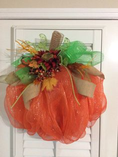 Get ready for fall with this deco mesh pumpkin wreath. It is constructed with orange poly deco mesh and accented with coordinating green and burlap mesh ribbon, a red sunflower and fall leaves. The wreath measures approximately 24 inches across and would make a big impact on a front door.