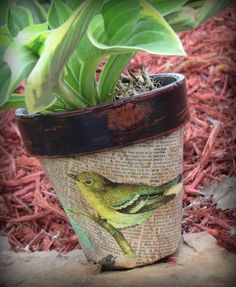 Decoupaged bird over typed print on distressed flowerpot.