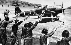 Chiran high school girls wave farewell with cherry blossom branches to departing kamikaze pilot in a Nakajima Ki-43-IIIa Hayabusa.