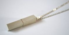 This is a unique, elegant concrete necklace with silver stripe on silver chain.  Each pendant is handmade, made of fine, high quality, gray concrete with shiny surface.  Details:  - Pendant: ca. 4,5 cm * 1 cm  - Chain: ca. 70 cm long  The necklace can be made in other forms or colors, so feel free to contact me, every individual requests are weolcome.