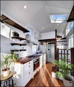 Custom Napa Edition by Mint Tiny Homes - Tiny Living The kitchen features a stunning wood counter with chevon pattern, white cabinets with leather pulls, white farm sink, and open wood shelving with black pipe brackets. Tiny House Company, Tiny House Plans, Tiny House On Wheels, Building A Tiny House, White Farm Sink, White Farmhouse, Casas Containers, Tiny House Living, Tiny House Kitchens