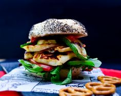 A stacked halloumi and red pepper burger layered in a bun with courgette, salad leaves and salsa. The vegetables and cheese are grilled for extra flavour and texture.