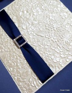 Ivory fold over with blue satin ribbon and crystal buckle. clovercreek.com