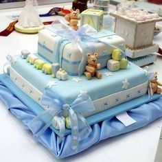 toy train and teddybears, and building blocks with letters and shapes, made from yellow and blue, green and white fondant, decorating a blue and white cake, with ribbons and bows