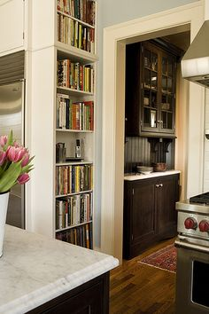 A built in bookshelf houses all the cookbooks and creates a convenient nook for the house phone to be nearby but out of the way.