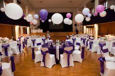 Lieu de réception violet parme mauve lilas Housses de chaises avec ruban en satin dans une salle des fêtes Boules japonaises chinoises suspendues rose blanc