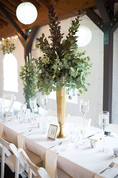 Natural greenery in tall centerpieces. Tall gold metal vases. King table design with Glass stemware vases and floating candles. Karrie Hlista design studio