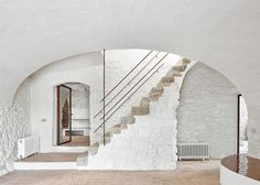 Arquitectura-G has revamped a country house into a family home featuring a tile-covered kitchen, a spiral staircase and a secluded swimming pool