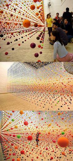 """""""Atomic: Full of Love, Full of Wonder"""" par Nike SAVVAS. Balles rebondissantes créant un champ dense de couleur dans l'espace, déplacé par un ventilateur à proximité. Installation au centre australien d'àrt contemporain de Melboune."""