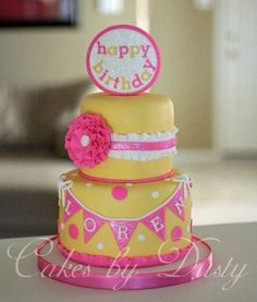 Cute pink and yellow birthday cake with ruffle flower and bunting.