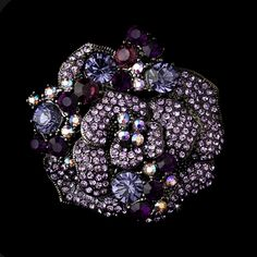 """This lovely floral brooch features dozens of genuine amethyst, lilac and violet opal crystals and rhinestones. This perfect brooch is an ideal accessory for any elegant occasion.This can be worn as a pin or in the hair with a slide on comb.Size: 2"""" x 2"""""""