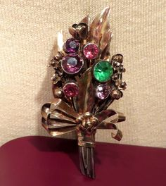 Stunning  Hobe beautiful floral bouquet vermeil brooch from the 1940's. Marked Hobe Sterling 14K.  The flowers are bezel set pink, amethyst colored,