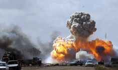 Vehicles belonging to forces loyal to Libyan leader Muammar Gaddafi explode after an air strike by coalition forces, along a road between Benghazi and Ajdabiyah March 20, 2011. REUTERS/Goran Tomasevic