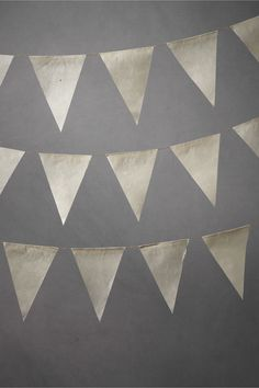 """Parchment Pennant Garland (5) $26.00 WRITE A REVIEW STYLE: 20826384 Pennants in a crisp, clean parchment to catch and release the afternoon's last rays of sun. Set of 5 strands Each strand: 15 pennants Each pennant: 7""""L, 5""""W at widest points Total length: 8' Lokta paper, hemp string Handmade in Nepal Exclusive to BHLDN"""