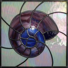 A square leaded glass panel with a single dramatic image of a fossil ammonite in streaky purple/blue glass, cut to allow the grain of the glass to flow around the image. It measures x and has a clear rippled glass background. Stained Glass Projects, Stained Glass Patterns, Mosaic Windows, Gold Angel Wings, Ammonite, Leaded Glass, Glass Design, Glass Ornaments, Glass Panels
