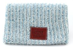 This beanie is knit from 100% cotton yarn in white and teal colors and features a brown leather patch debossed with the Love Your Melon logo. One size fits all. Made in the USA. Machine washable. Fift