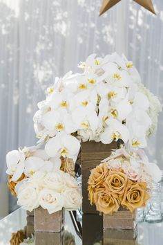 The mirrored bar was topped with short floral arrangements composed of white and gold roses, orchids, and hydrangea blossoms. #flowerarrangement #centerpiece  Photography: Samuel Lippke Studios