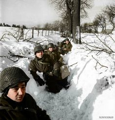 American soldiers crouch in a ditch in Belgium, during the Battle of the Bulge. January, 1945
