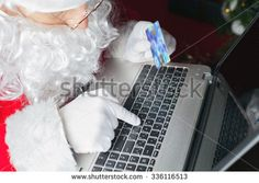 Santa buying by plastic card Christmas gift or present by online payment through the Internet Banking. Close-up of Santa hand and laptop, holding gift box. Shopping indoor at home