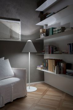 Apartment : Simply Brilliant Apartment In Piacenza Designed by Studio Blesi Subitoni - One of Corners Look of Apartment in Piacenza by Studio Blesi Subitoni showing Floating Wall Bookshelves and Floor Lamp and Slipcovered Arm Chair and Wood Flooring Tile medium version
