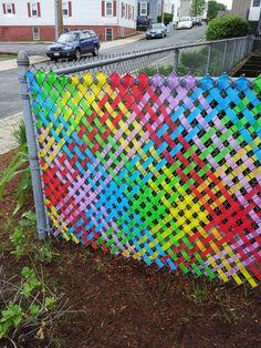 Забор из рабицы, украшенный цветным скотчем.