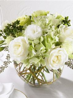 White and light green roses, green hydrangea and green carnations along with white lisianthus accented with seeded eucalyptus and curly willow arranged in a clear glass bubble bowl.