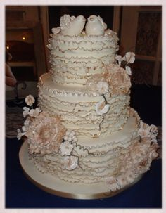 Ruffles tipped in gold, peonies, cherry blossoms, sweet peas and berries topped with little love birds.  Cakes So Special by Denise Talbot